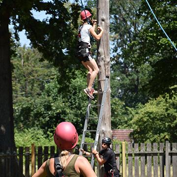 Eine Person klettert über ein Seil