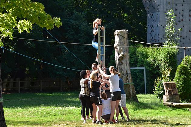 Eine Gruppe von Menschen halten eine Leiter während eine Person hinaufklettert.