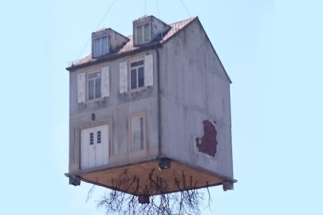 Ein komplettes Haus das von einem Krahn angehoben wird