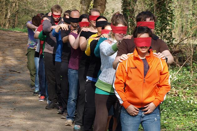 Eine Gruppe von Menschen bildet mit verbundenen Augen eine Kette