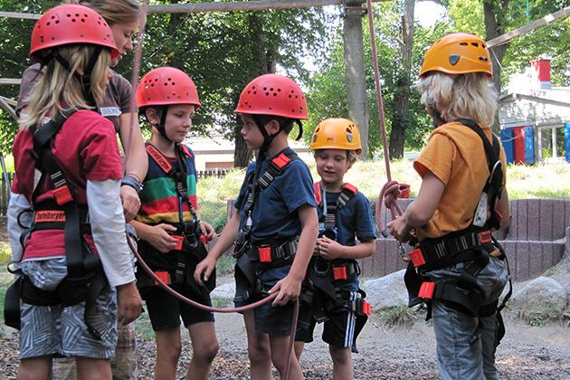 Eine Gruppe von Kindern wird für den Kletterpark von einer Mitarbeiterin vorbereitet