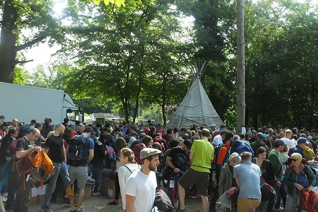 Eine große Menschengruppe im Hintergrund ein Tipi Zelt
