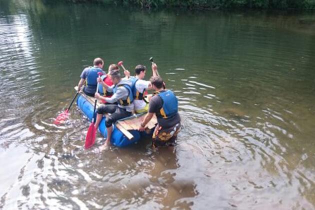 Eine Gruppe von Menschen im Wasser auf einem selbstgebautem Floß