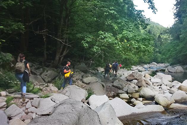 Menschen wandern an einem Fluss entlang