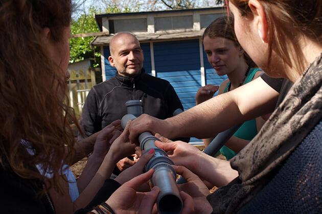 Personen bilden unter aufsicht ein zusammenhängendes Rohr