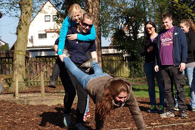 Eine Person trägt eine andere Person auf dem Rücken. Gemeinsam halten sie eine weitere Person an den Beinen fest.