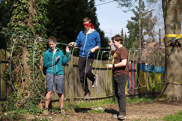 Eine Person läuft mit verbundenen Augen über ein Balanceseil. Zwei Personen helfen dabei.